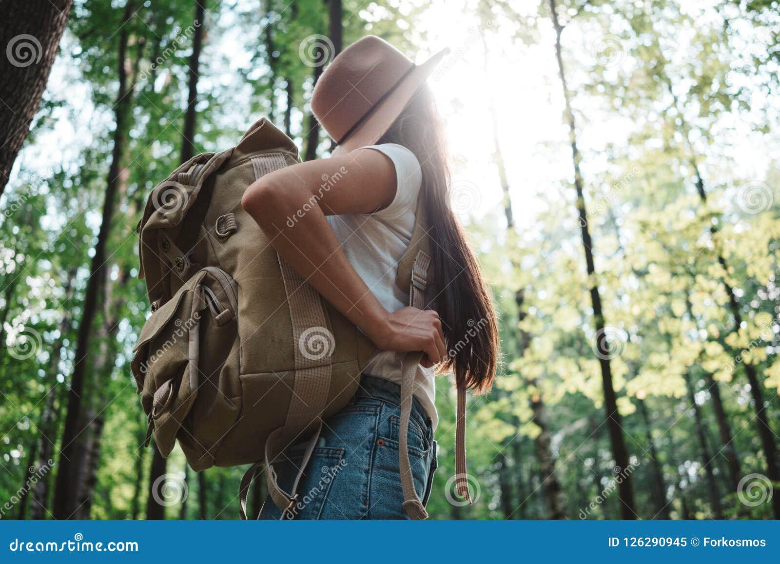 Muchacha del inconformista que viaja solamente y que mira alrededor en bosque en mapa de ubicación de la mochila y del control de