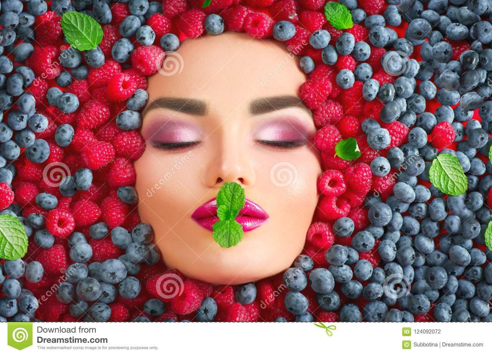 Muchacha del modelo de moda de la belleza que miente en bayas maduras frescas Haga frente en primer colorido de las bayas Labios