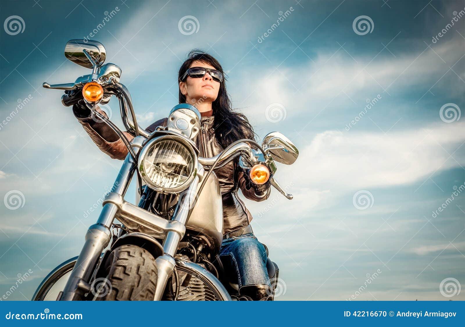 Muchacha del motorista en una motocicleta