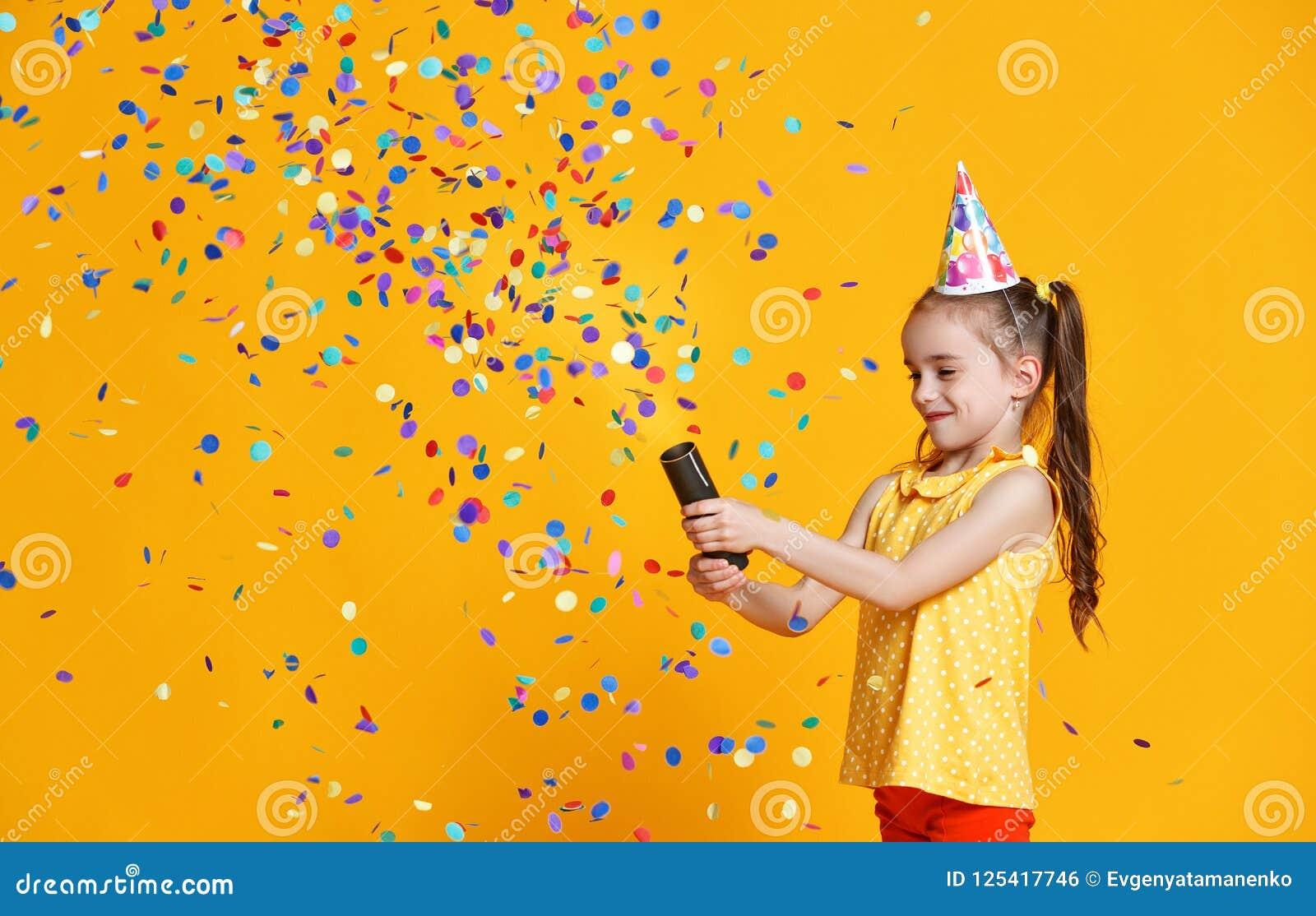 Muchacha del niño del feliz cumpleaños con confeti en fondo amarillo