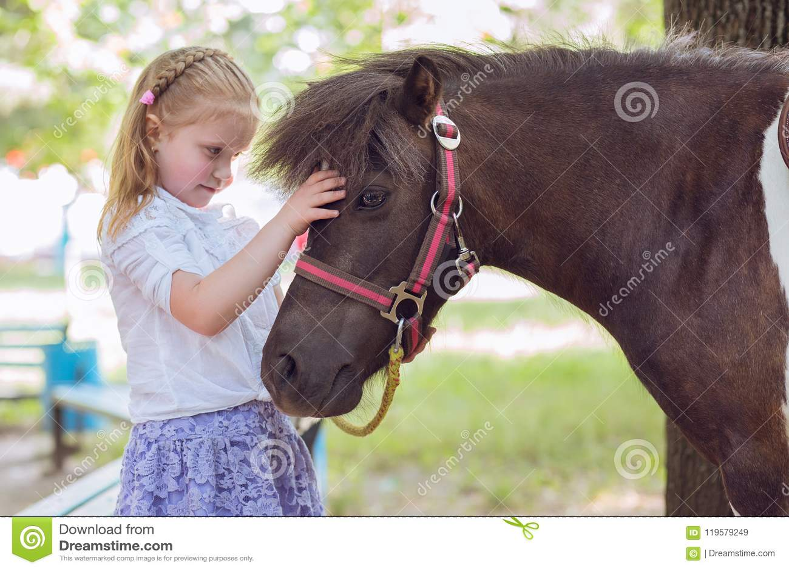 Muchacha del niño que celebra el abrazo de su fondo verde del parque del exterior del caballo del potro al aire libre