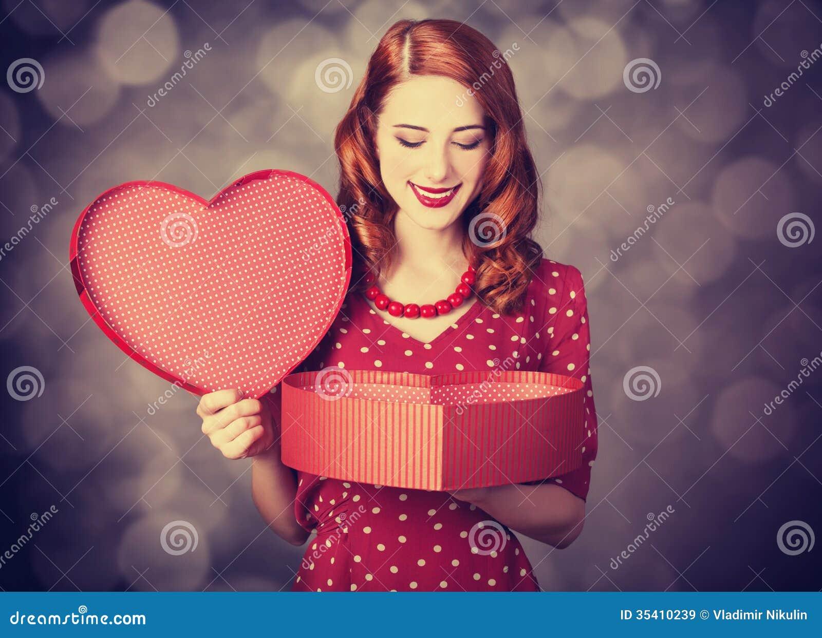 Muchacha del pelirrojo con el regalo para el día de tarjetas del día de San Valentín