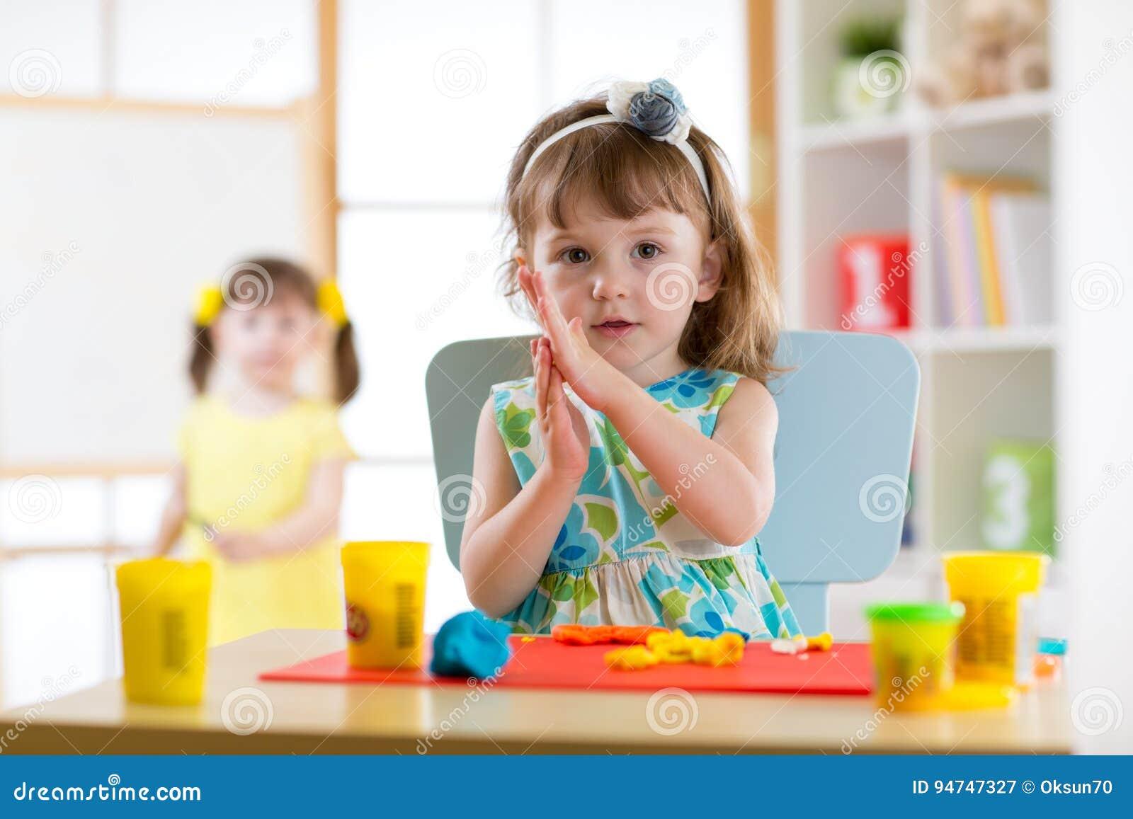 Muchacha del preescolar que se divierte así como la arcilla de modelado colorida en una guardería Niño creativo que moldea en cas