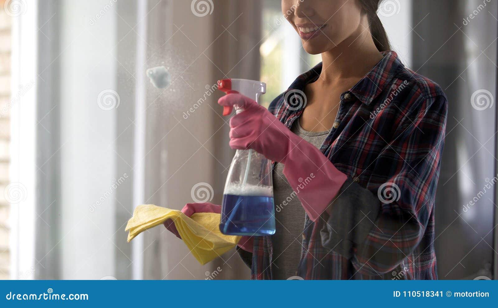 Muchacha del servicio de la limpieza que aplica agentes de limpiamiento a las superficies de cristal polvorientas
