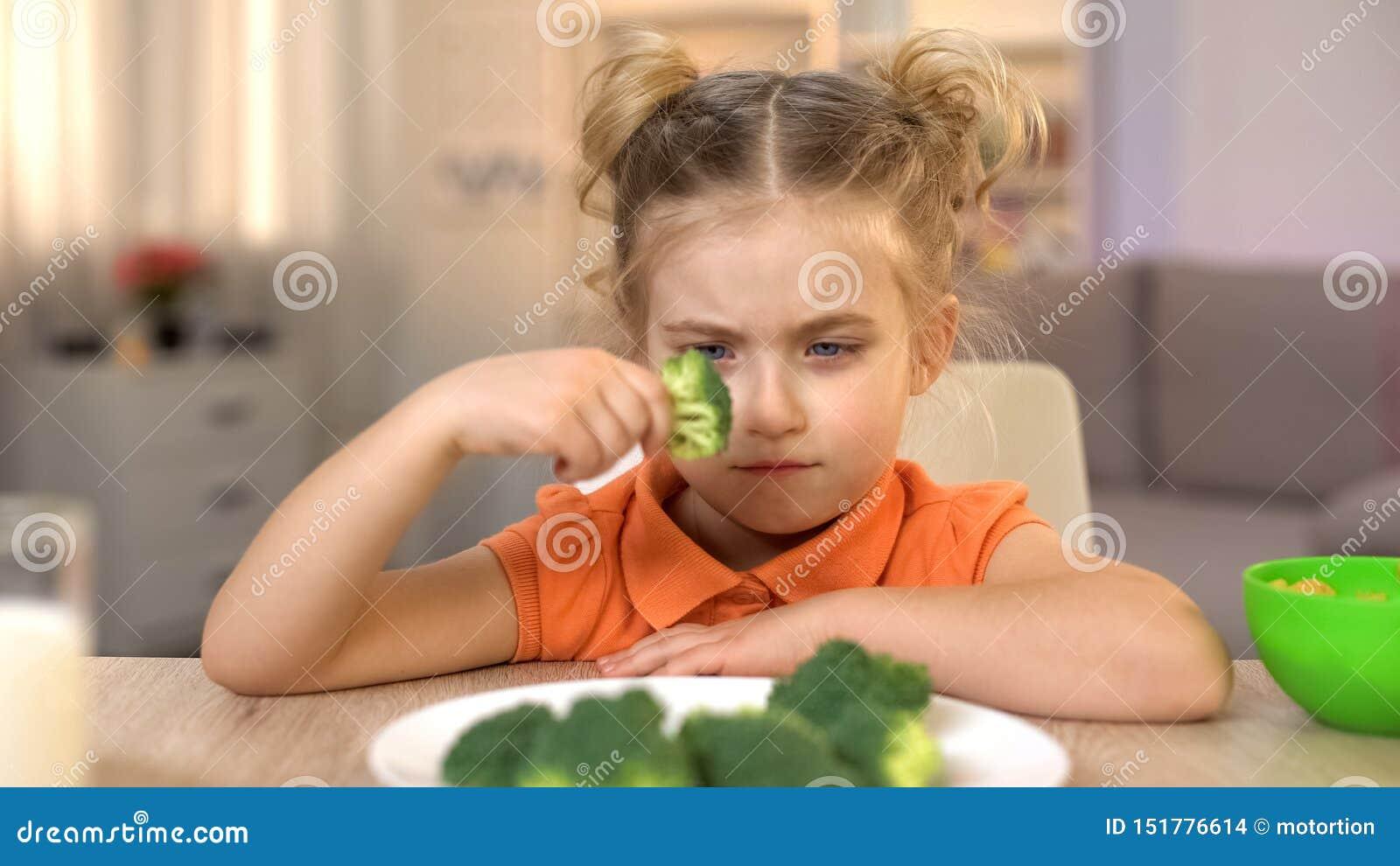 Muchacha del trastorno que mira el bróculi con el repugnancia, lleno de vitaminas pero de comida insípida