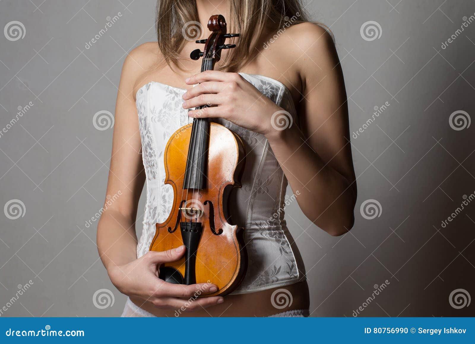 Muchacha delgada atractiva en el corsé blanco que sostiene un violín