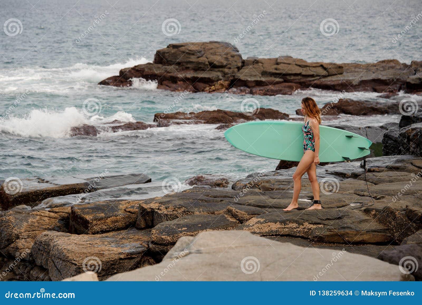Muchacha deportiva en el traje de baño coloreado multi que camina con la resaca en las rocas en la playa