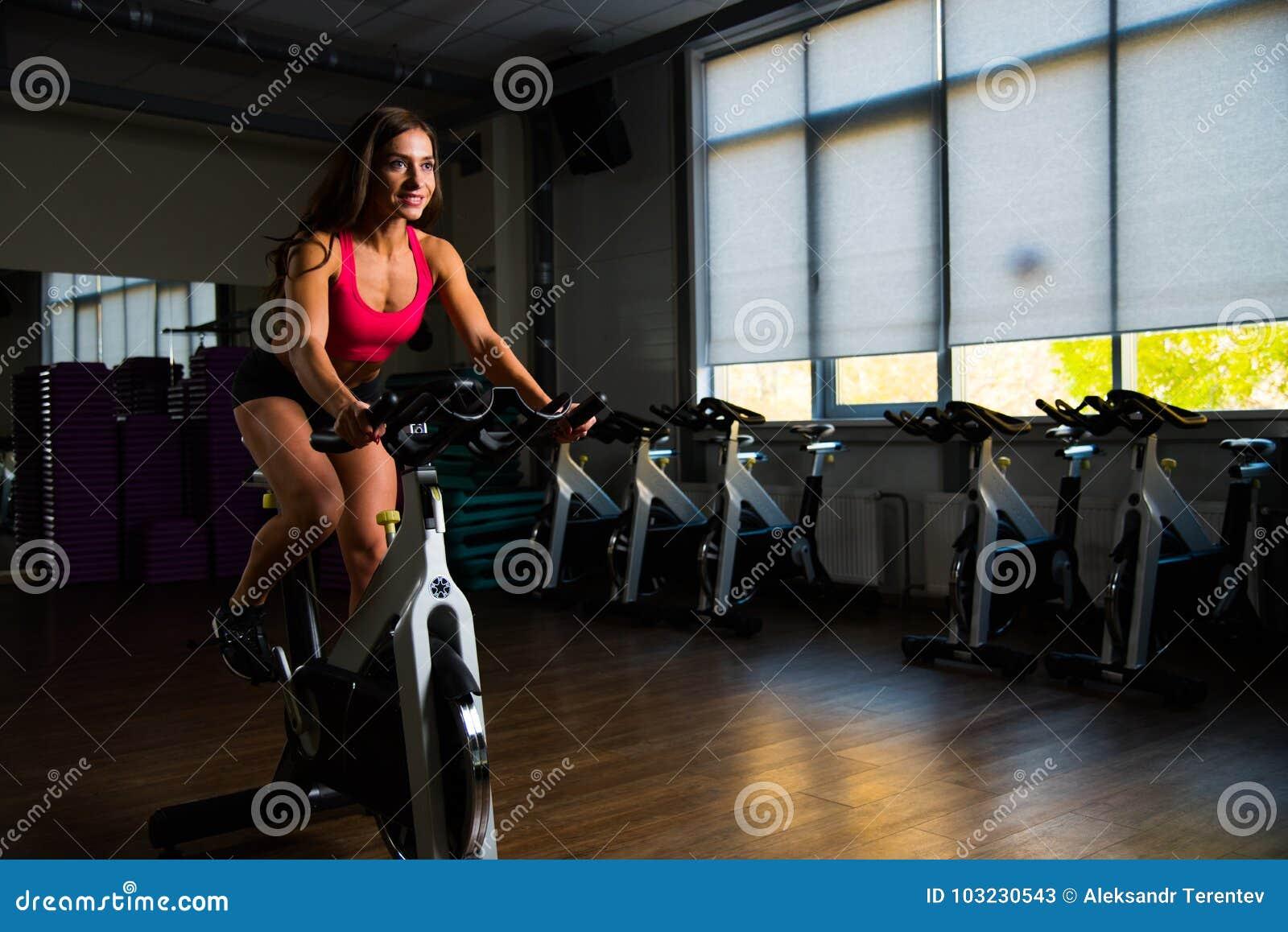 Muchacha deportiva en pasillo de la aptitud en ciclo