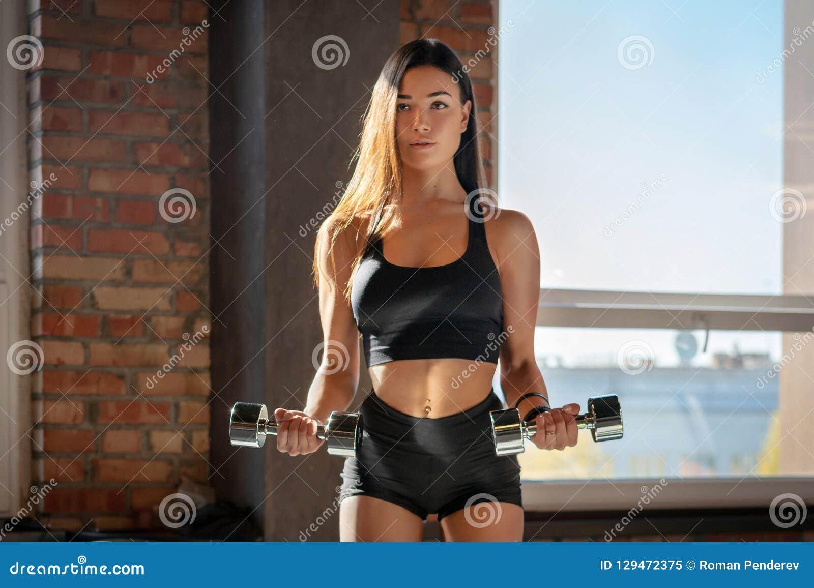 Muchacha deportiva que hace ejercicio con pesas de gimnasia