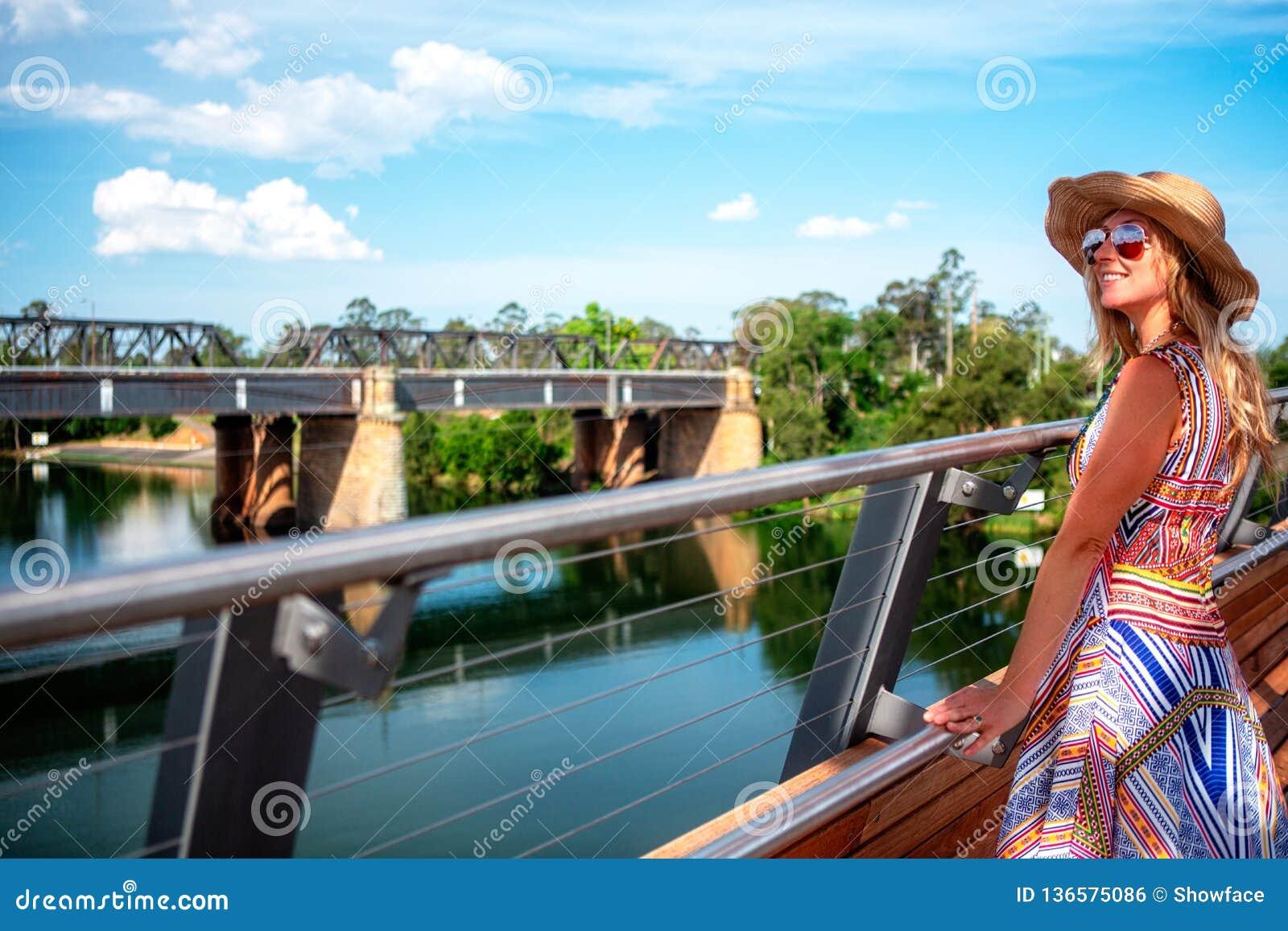 Muchacha despreocupada que disfruta de las opiniones del río del puente en Penrith
