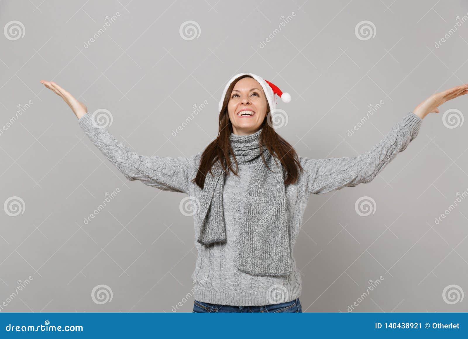 Muchacha divertida de Papá Noel en el sombrero gris de la Navidad de la bufanda del suéter que mira para arriba, separándose seña
