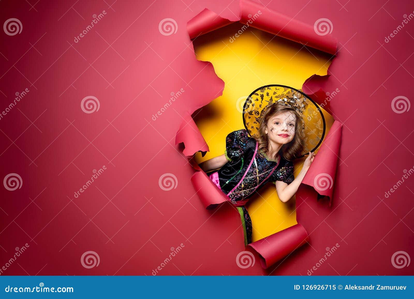 Muchacha divertida de risa del niño en un traje de la bruja en Halloween