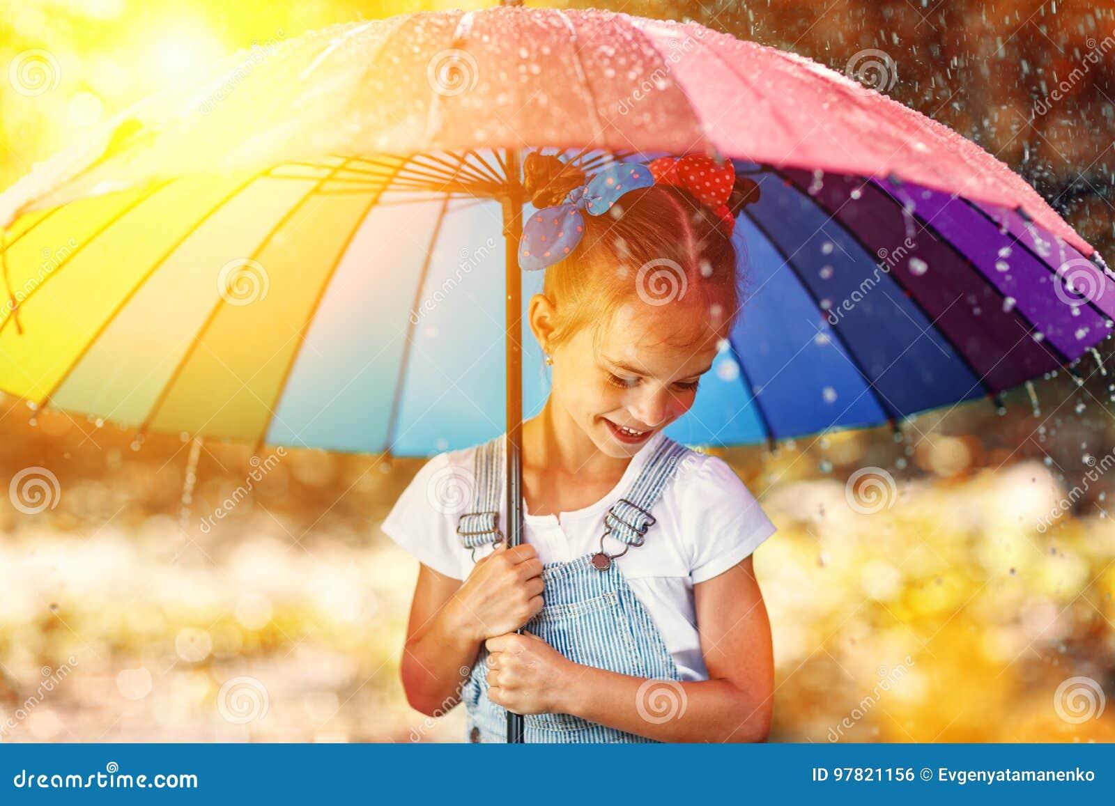 Muchacha divertida feliz del niño con el paraguas que salta en charcos en rubb