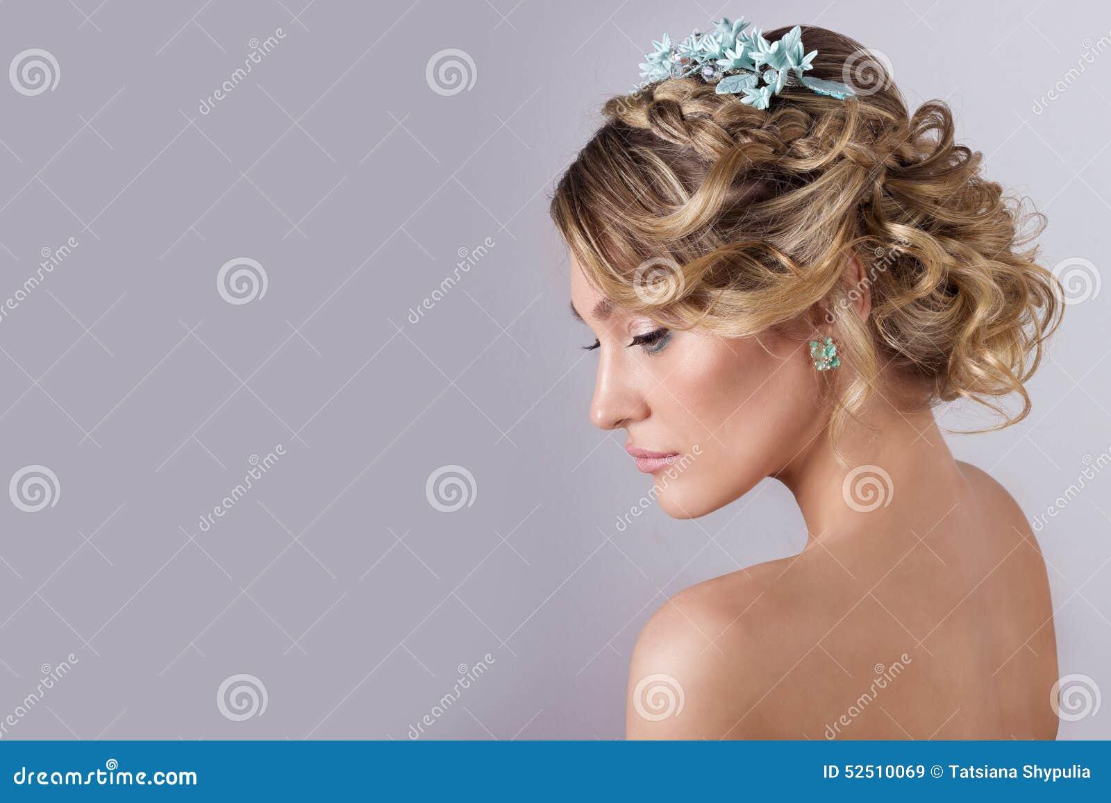 Muchacha dulce elegante atractiva joven hermosa en la imagen de una novia con el pelo y las flores en su pelo, maquillaje delicad