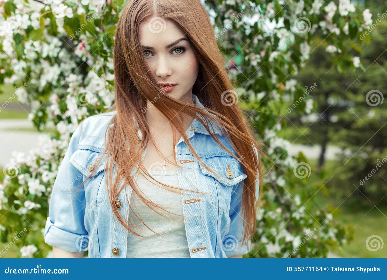 Muchacha dulce linda atractiva hermosa con el pelo rojo largo y los ojos verdes en una chaqueta del dril de algodón cerca de un á