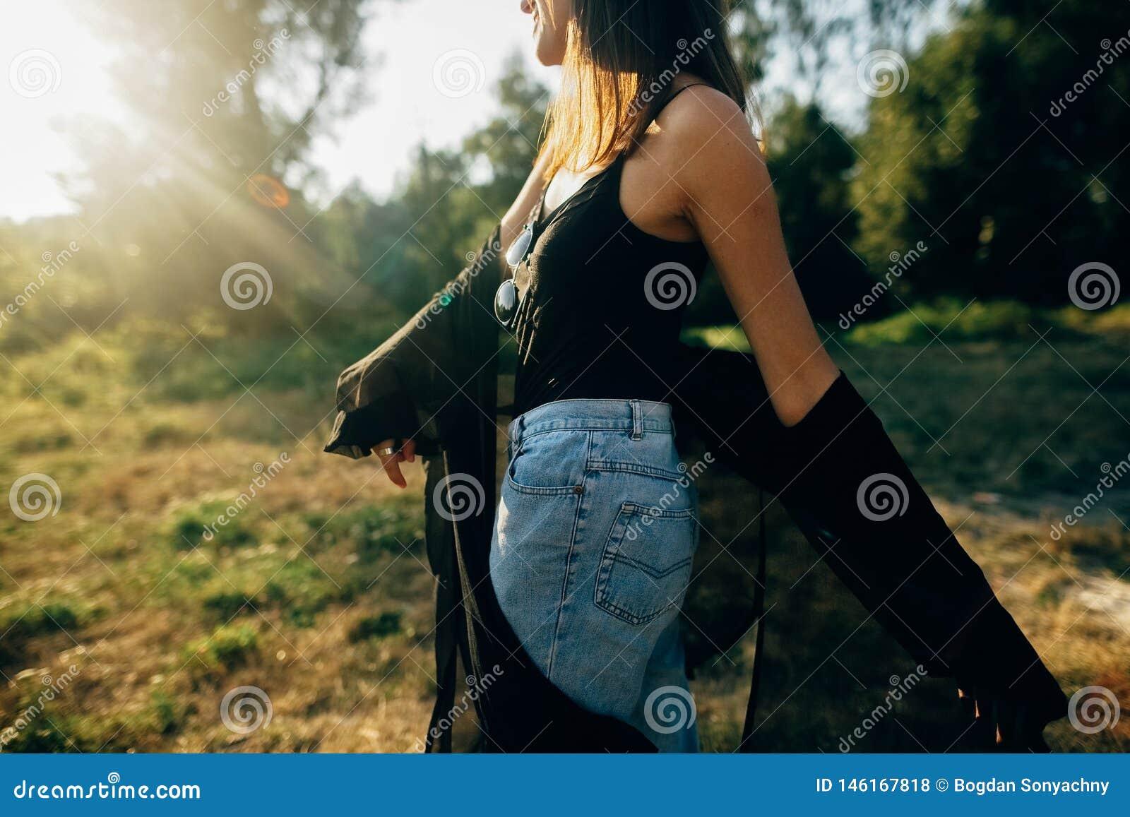 Muchacha elegante del inconformista que se divierte en el parque soleado en rayos de sol que sorprenden, momento atmosf?rico Bail