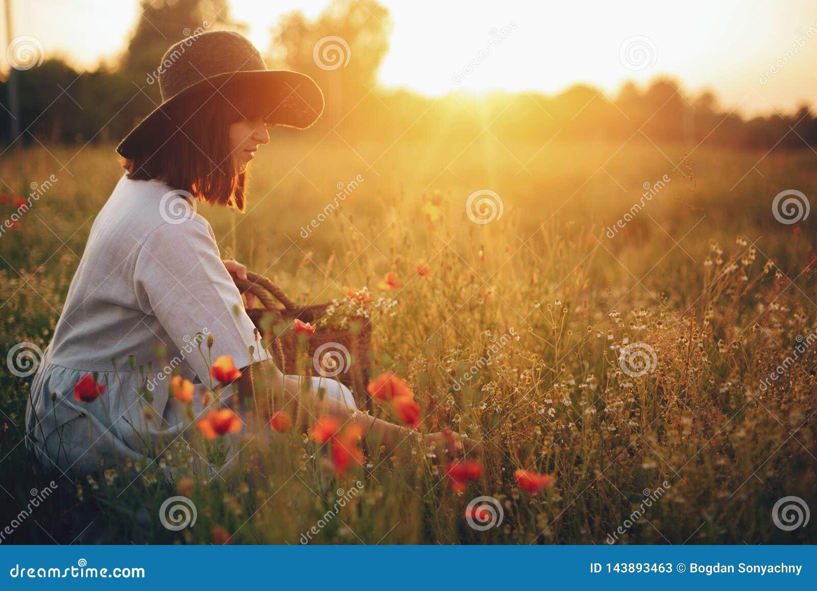 Muchacha elegante en el vestido de lino que recolecta las flores en la cesta rústica de la paja, sentándose en prado de la amapol