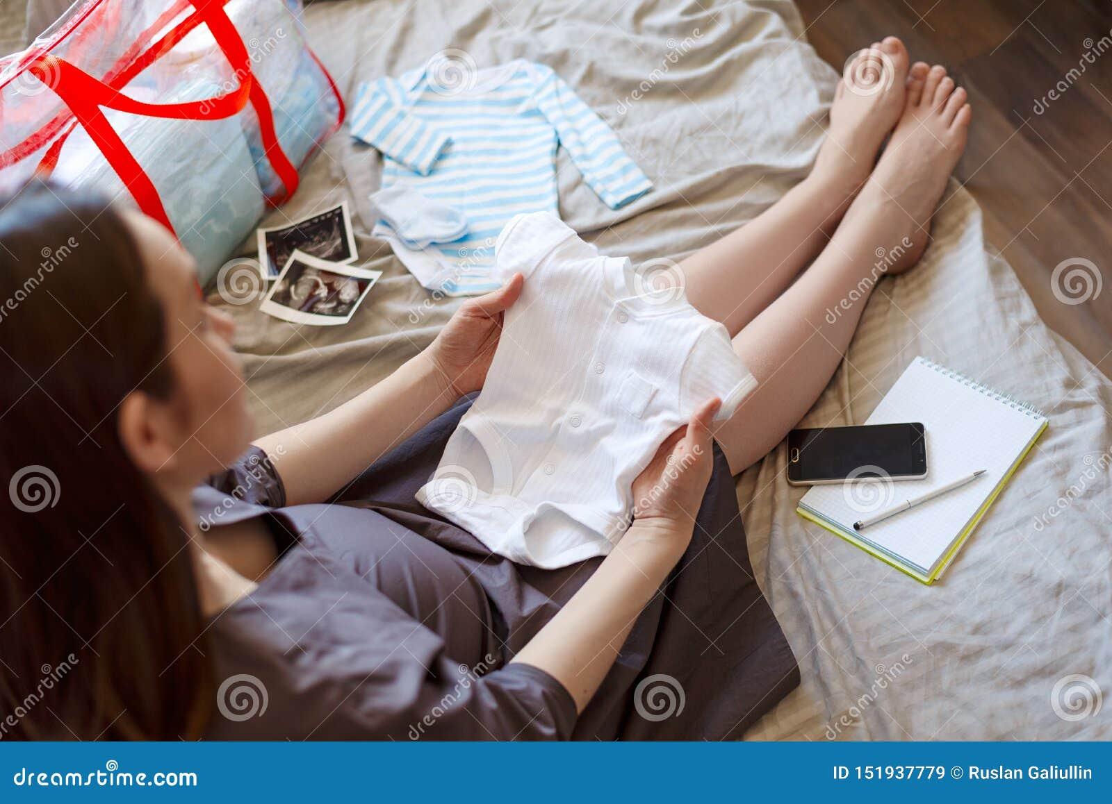 Muchacha embarazada que se sienta en la cama que sostiene una blusa del bebé, tarifas en el hospital