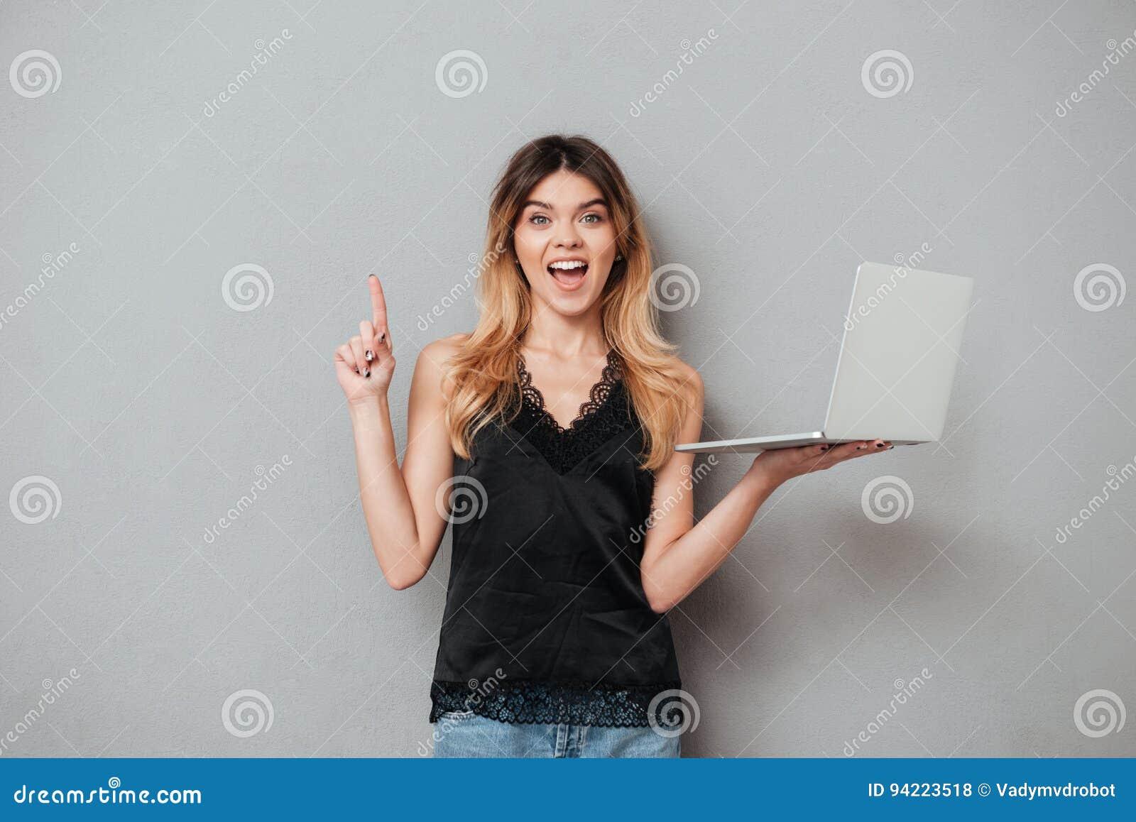 Muchacha emocionada que sostiene el ordenador portátil y que destaca el finger en el copyspace