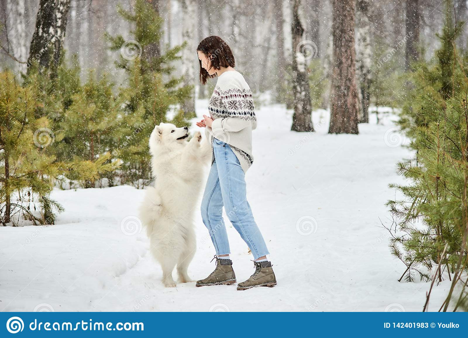 Muchacha en el bosque del invierno que camina con un perro La nieve está cayendo