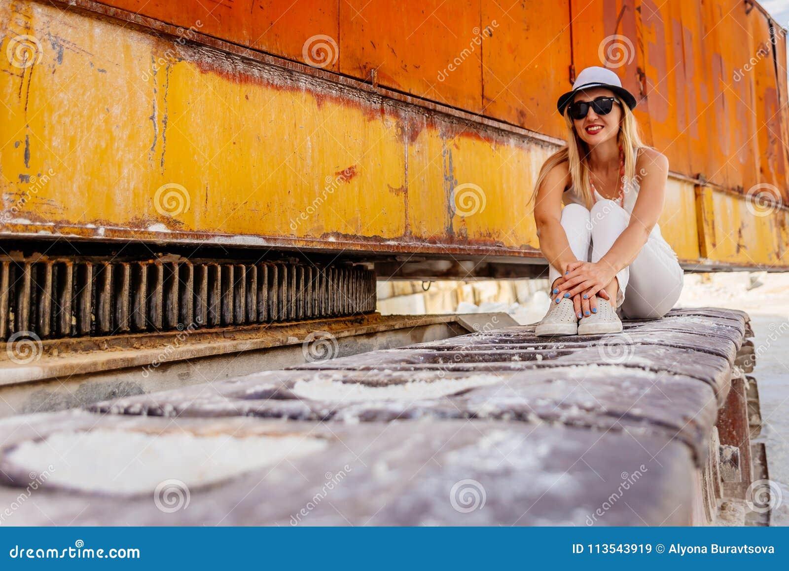 Muchacha en el sombrero y los vidrios que se sientan abrazando sus rodillas