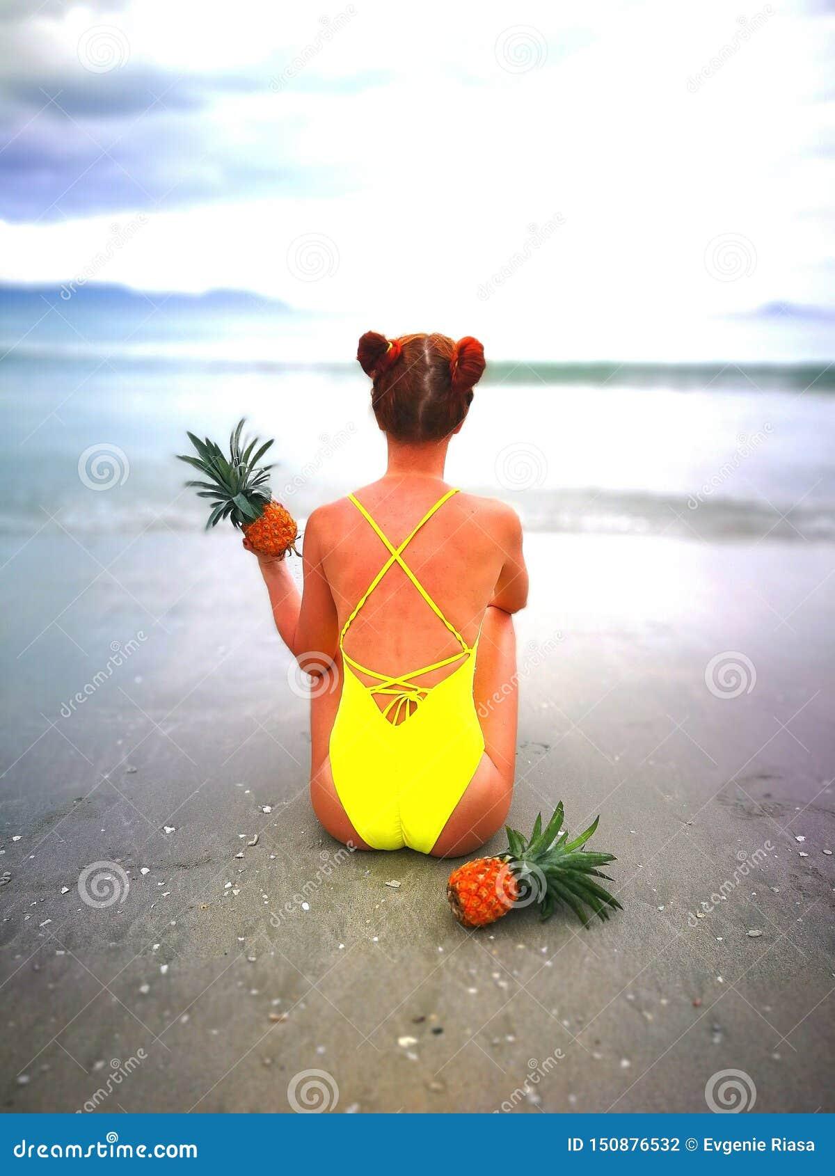 Muchacha en el traje de baño amarillo que se sienta en la playa en Nha Trang Vietnam