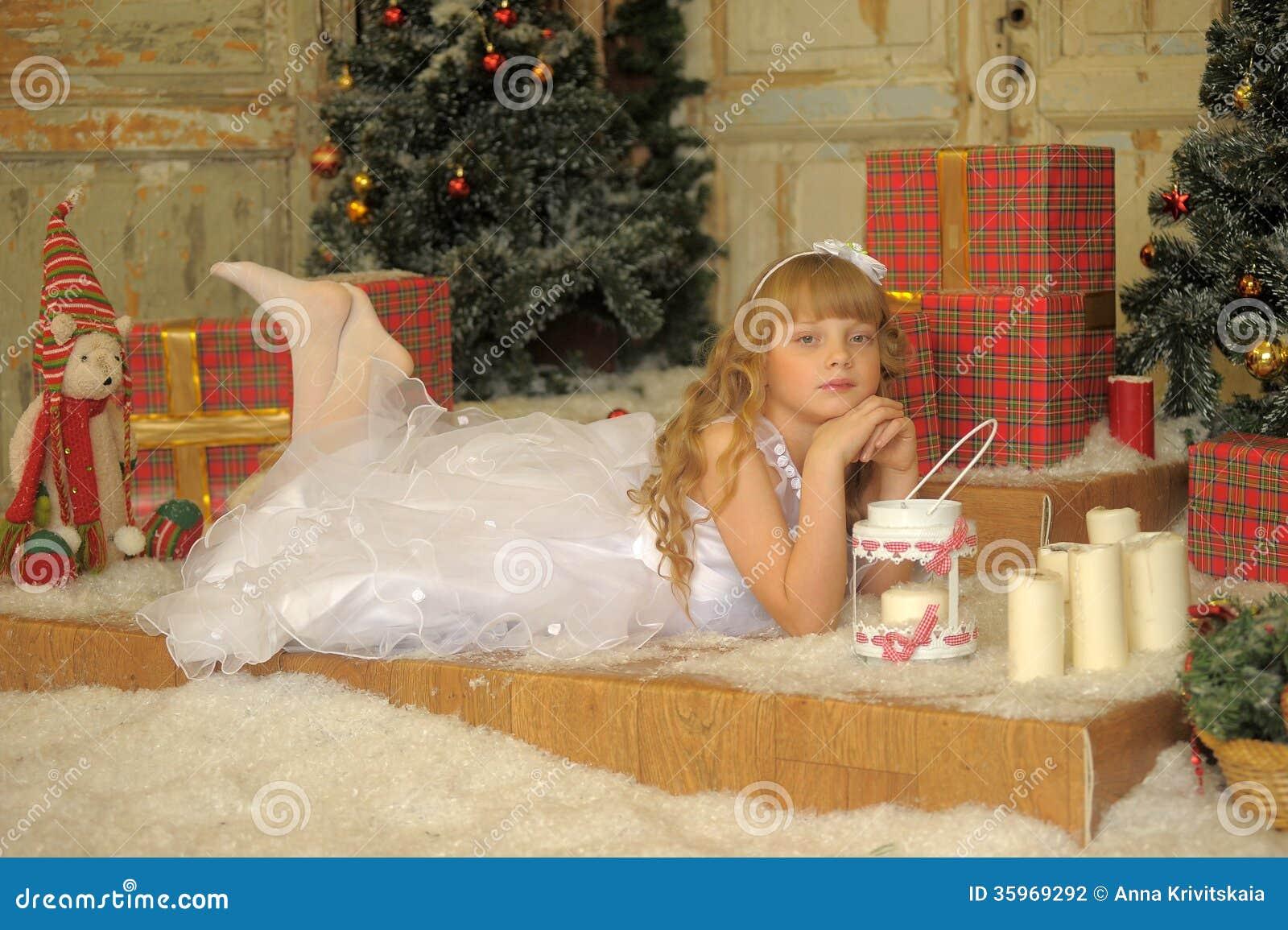 Muchacha en el vestido blanco en la Navidad