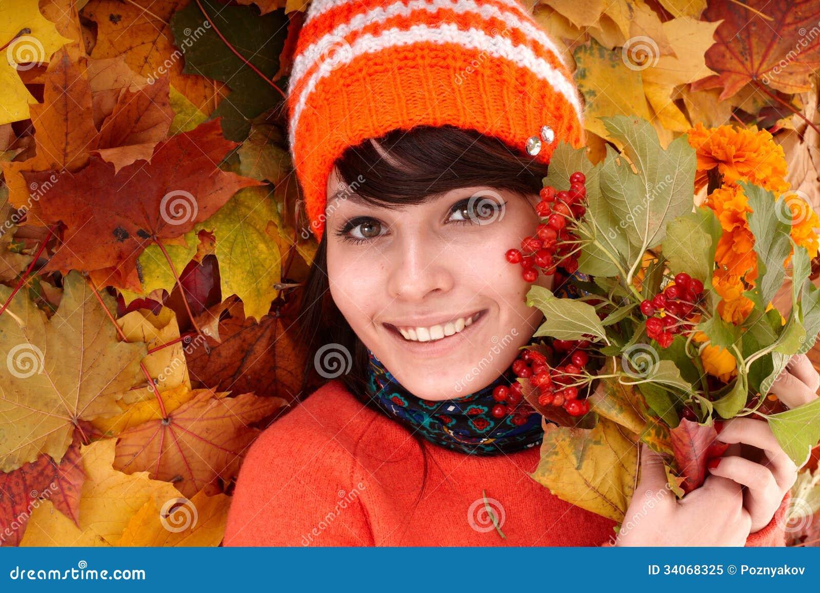 Muchacha en hojas anaranjadas del otoño.