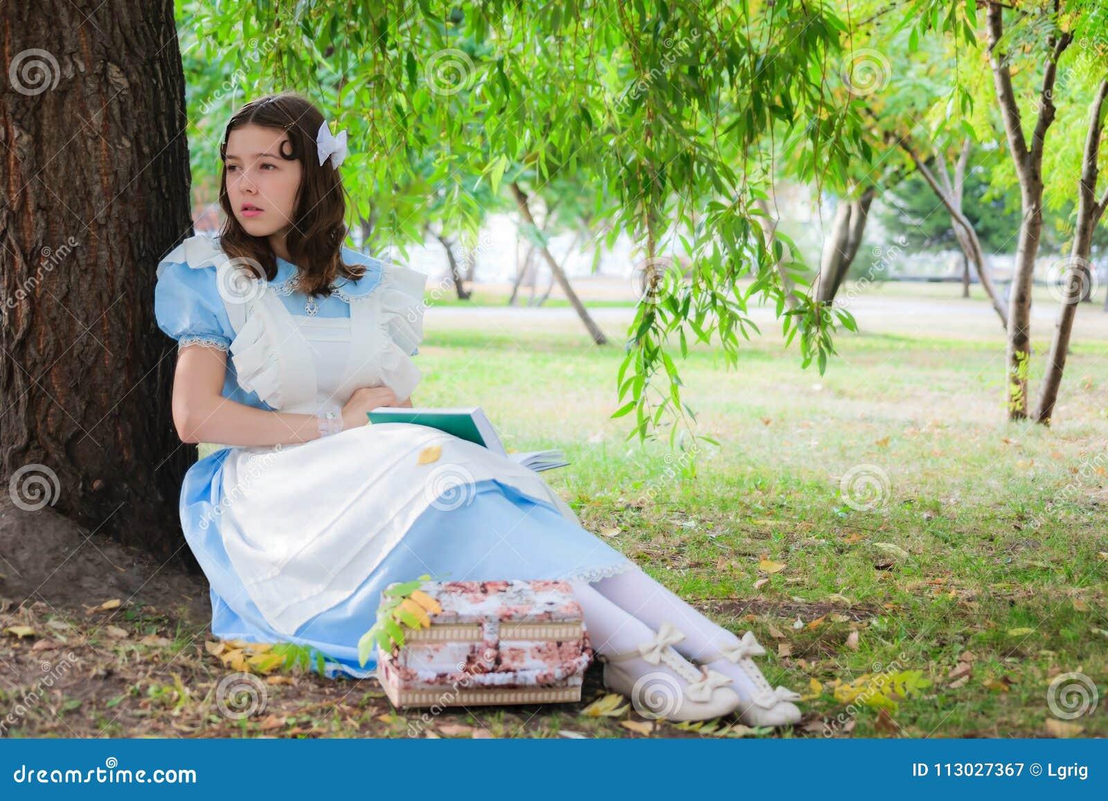 Muchacha en la imagen de la heroína de una hada que se sienta debajo de un árbol