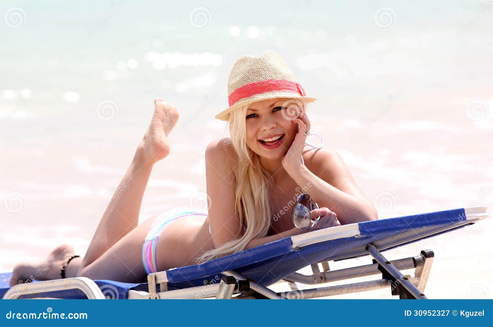 Muchacha en la playa. blonde atractivo el vacaciones. mujer joven hermosa feliz con el sombrero del verano