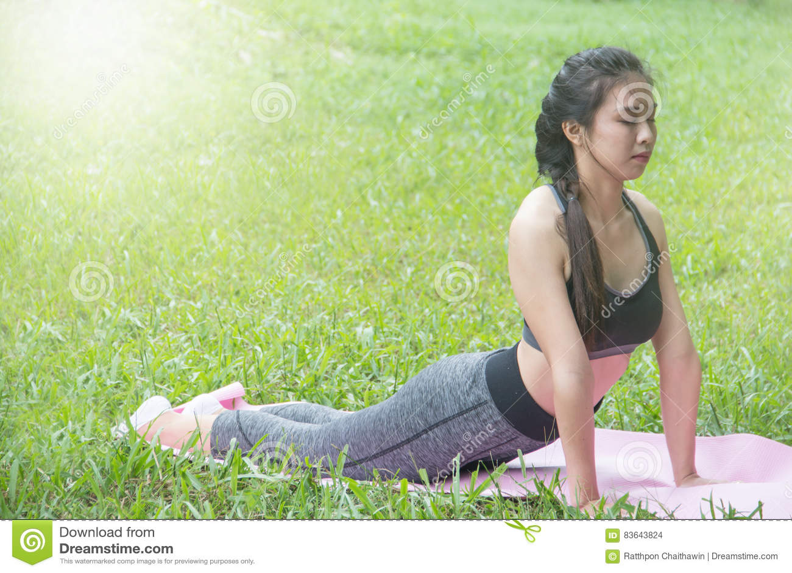 Muchacha en la ropa de deportes verde que hace yoga