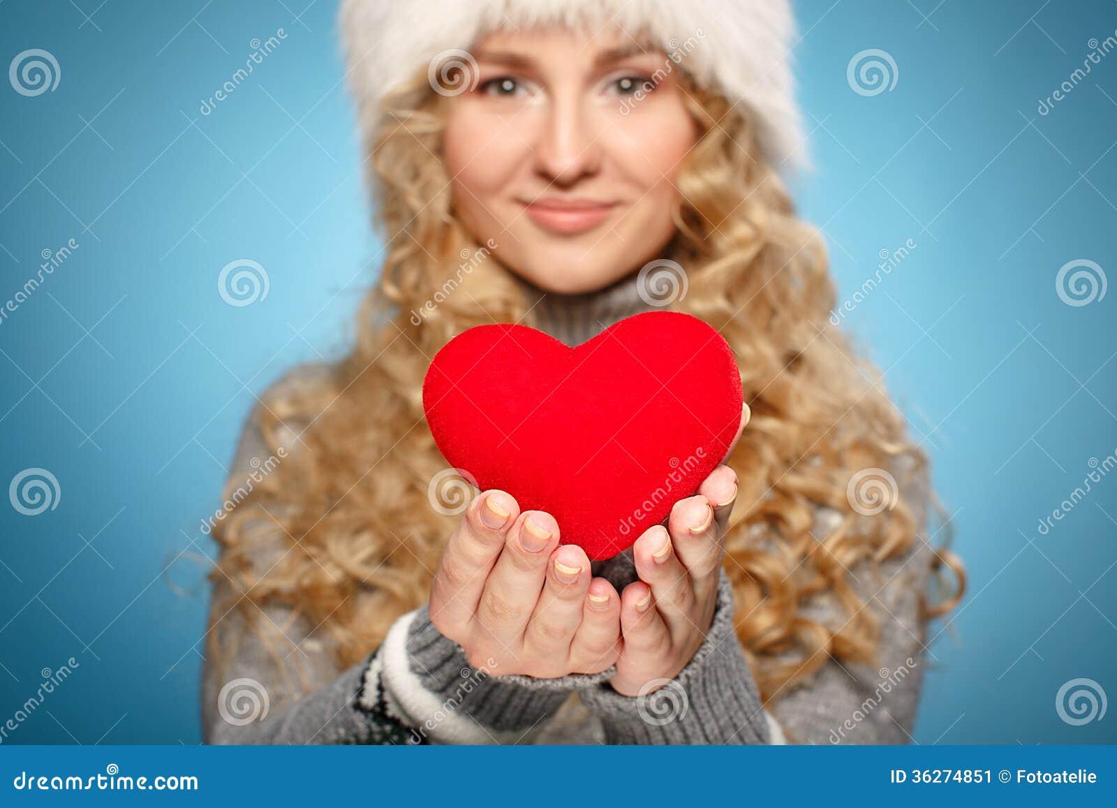 Muchacha en la ropa del invierno que da el corazón. Concepto del día de tarjeta del día de San Valentín
