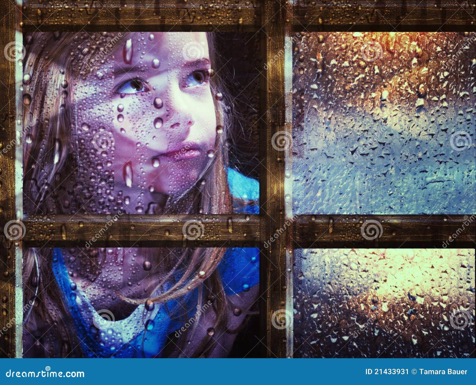 Muchacha en la ventana en lluvia