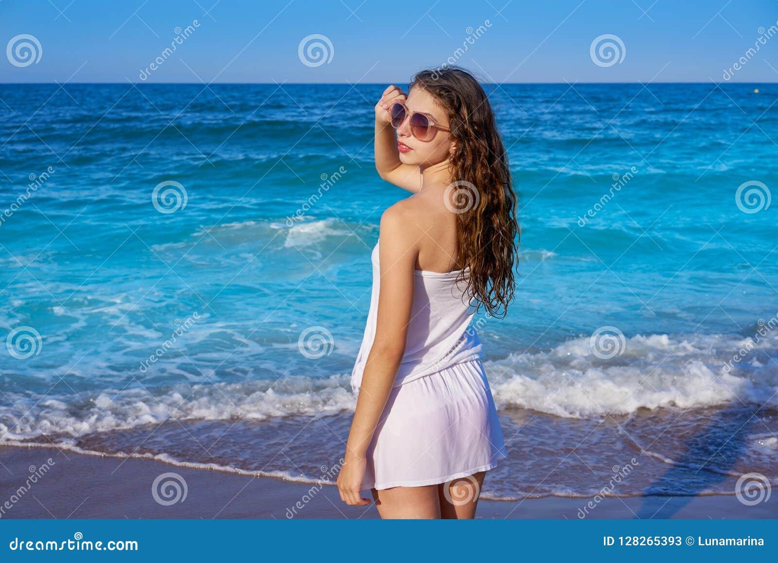 Muchacha en orilla de mar de la playa con el vestido del verano