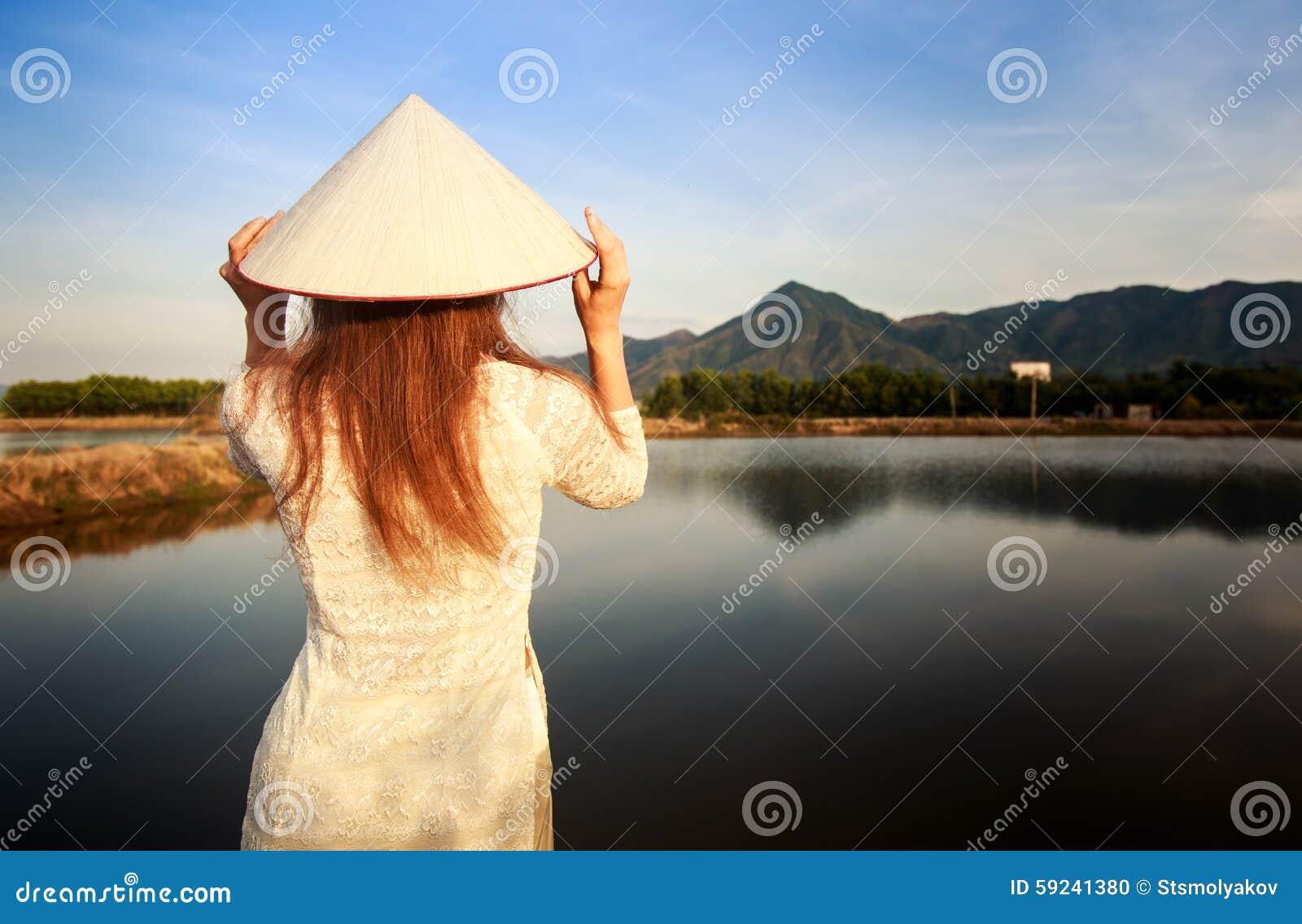 Muchacha en parte trasera vietnamita del sombrero contra los lagos del país