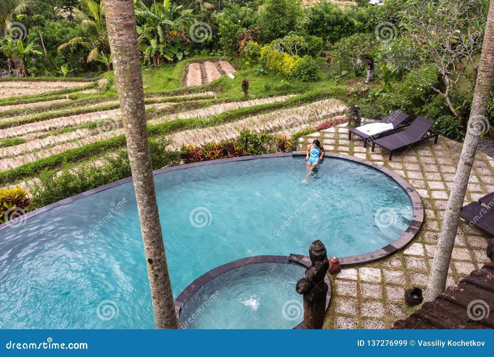 Muchacha en piscina del infinito hacia selva con palmtrees