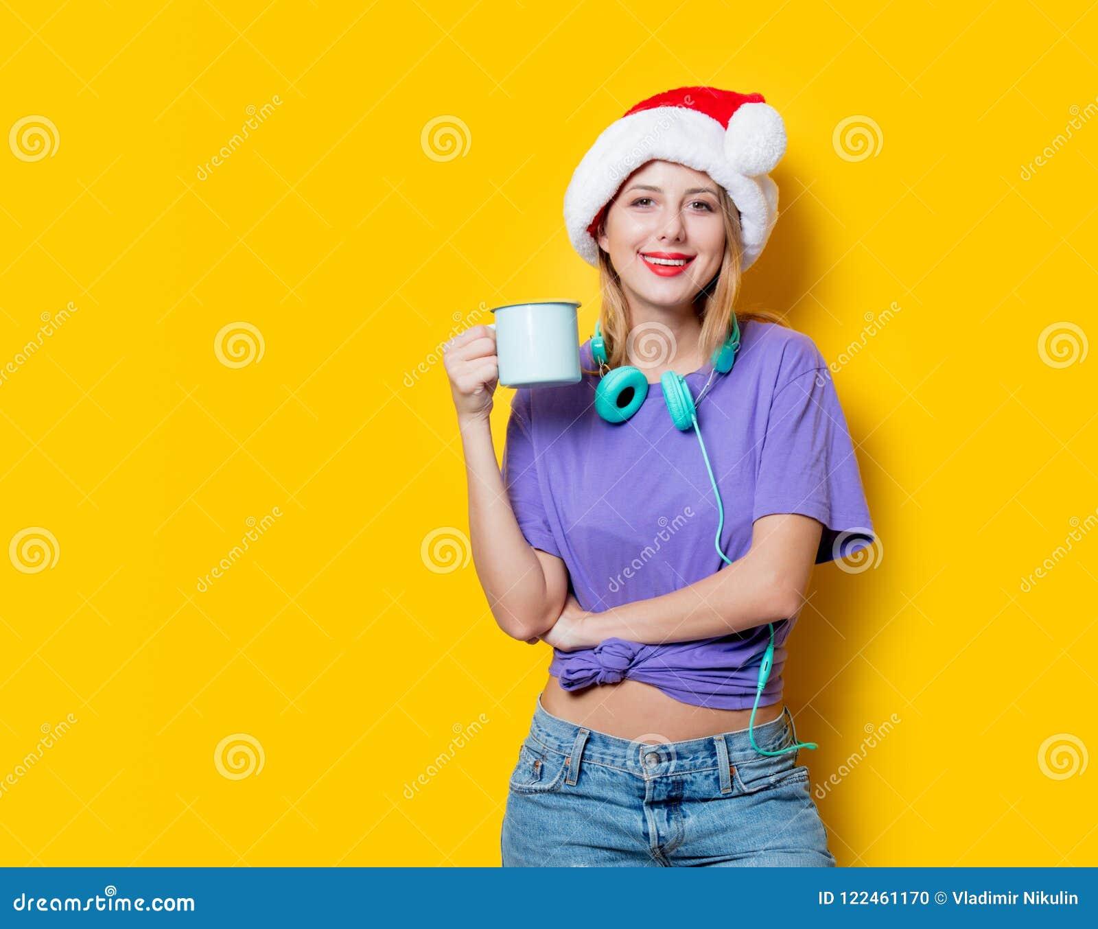 Muchacha en sombrero de la Navidad con la taza