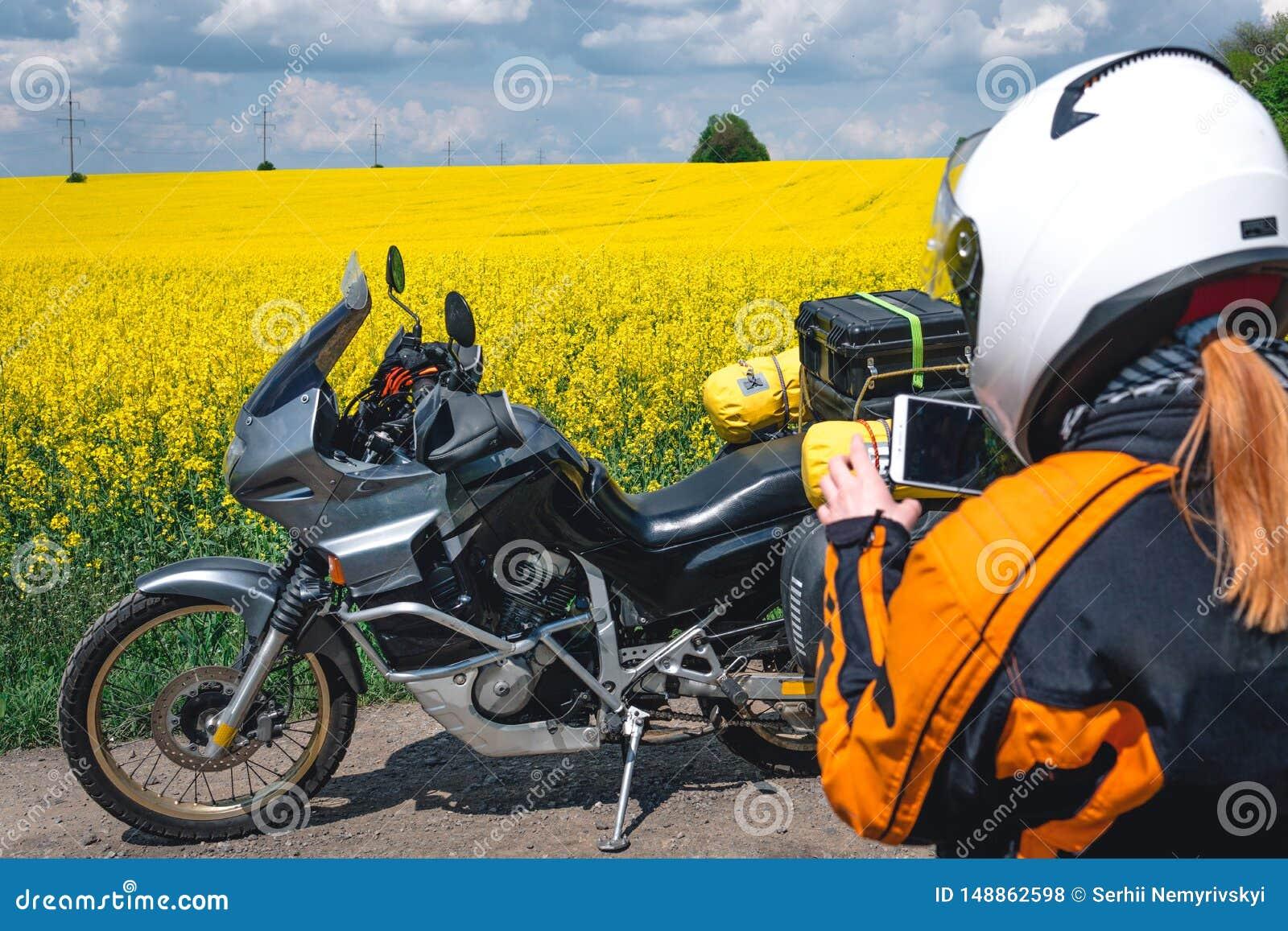 Muchacha en un equipo y vidrios de la protección con la motocicleta turística Campo de flores amarillo Viaje, enduro y apagado ca