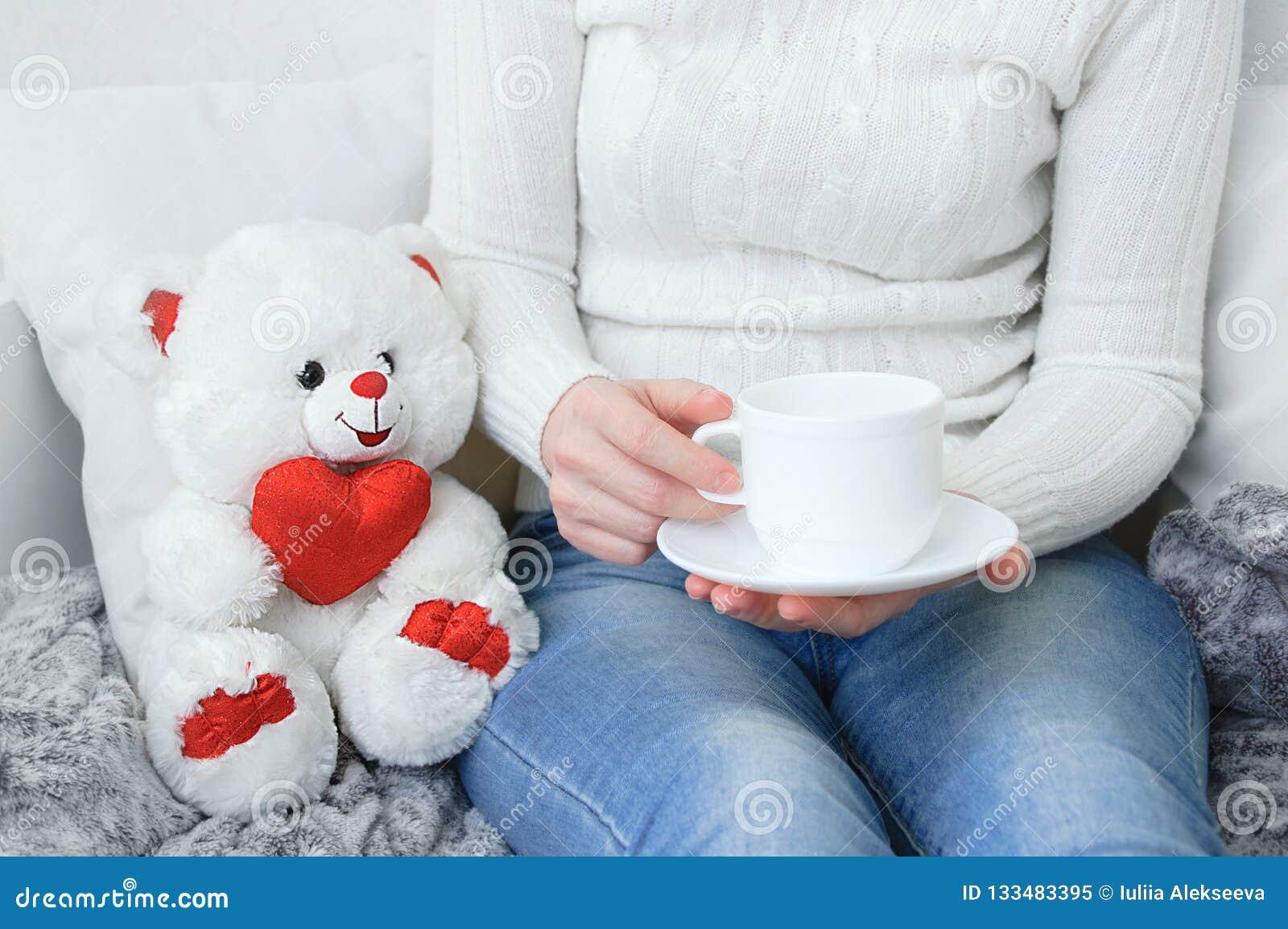 Muchacha en un suéter blanco y vaqueros en el sofá con una taza de café en sus manos
