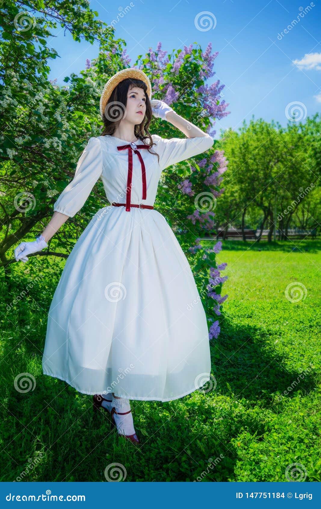 Muchacha en un vestido blanco y paseos del sombrero de paja