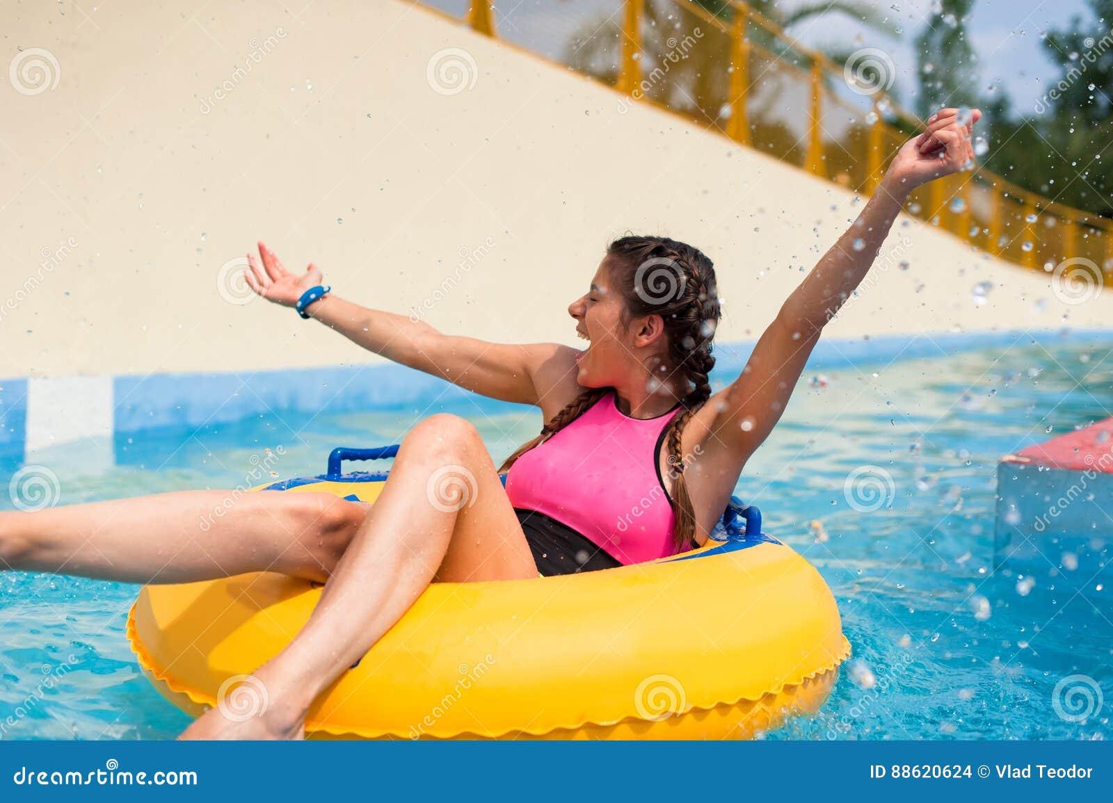 Muchacha en una piscina que se sienta en un flotador inflable de goma