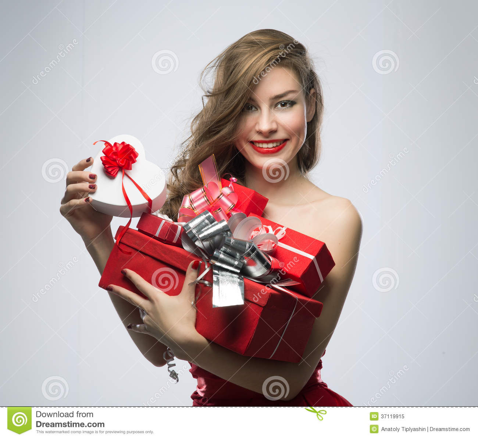 Muchacha en vestido rojo con los regalos el día de tarjetas del día de San Valentín
