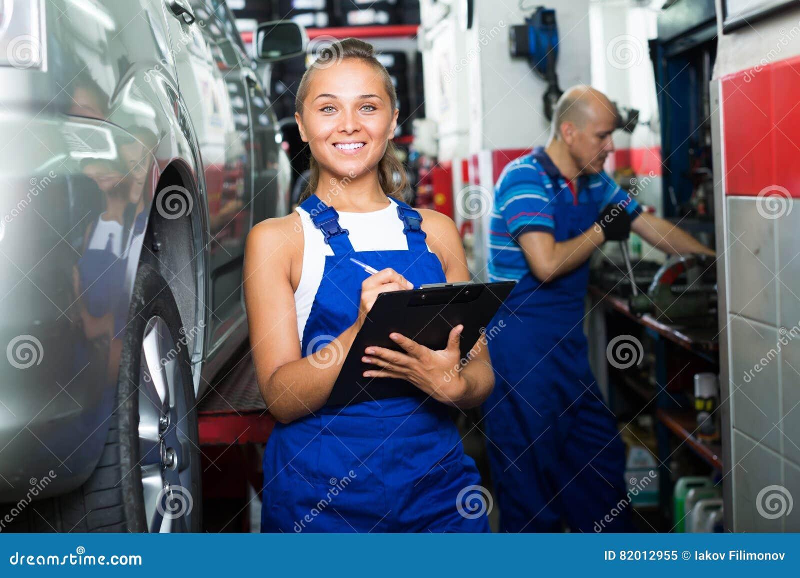 Muchacha en workwear en taller del mecánico de automóviles