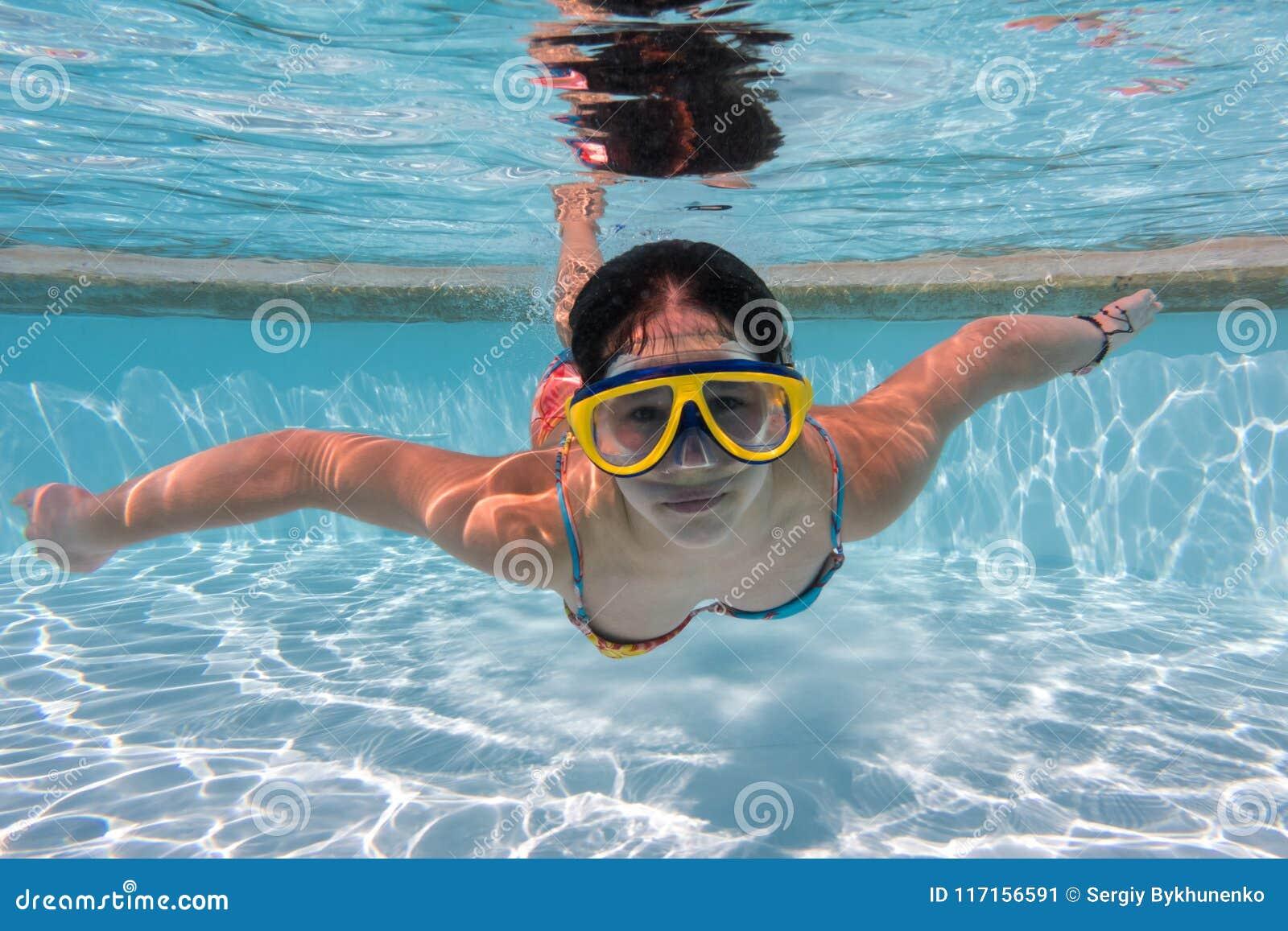 Muchacha en zambullida de la máscara en piscina