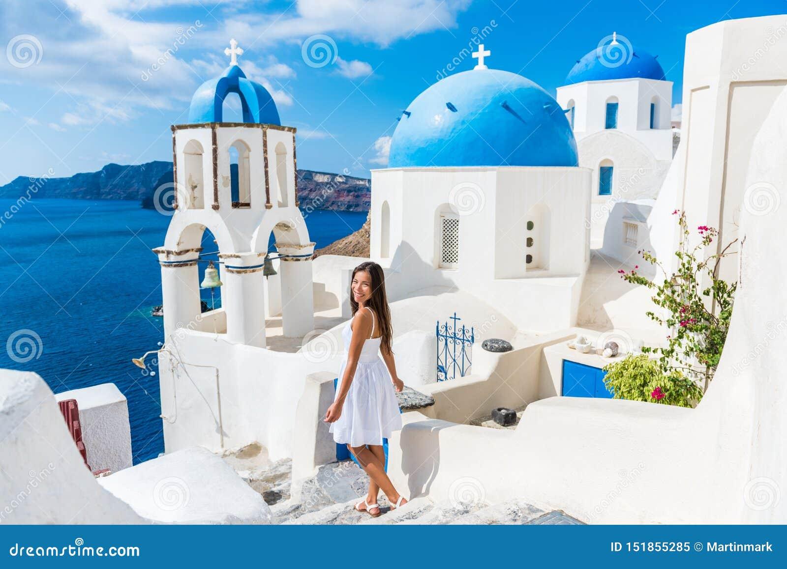 Muchacha europea de las vacaciones de verano que camina en las bóvedas de Oia