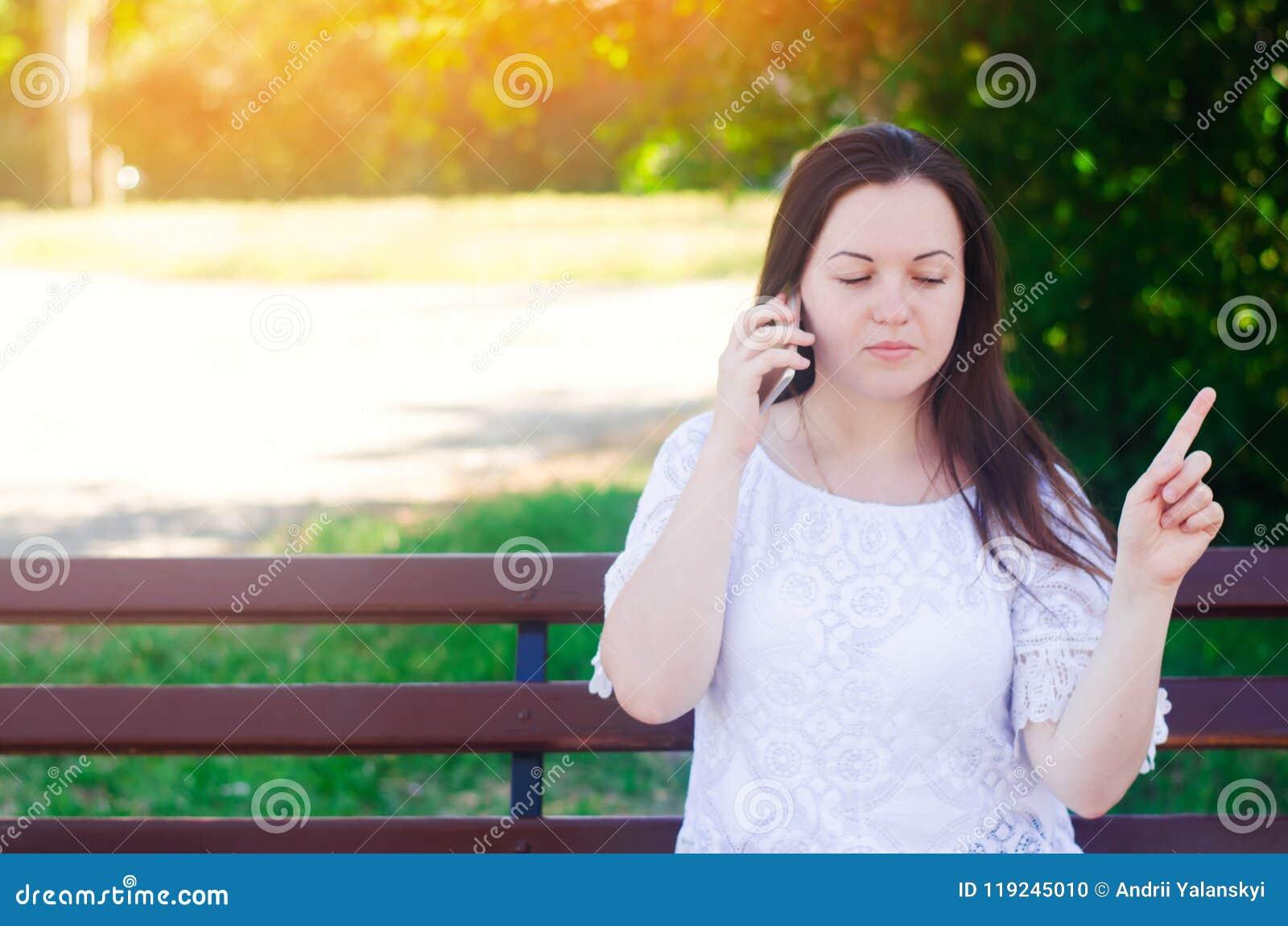 Muchacha europea hermosa joven que se sienta en un banco y que habla en el teléfono La muchacha señala un finger lejos, da consej