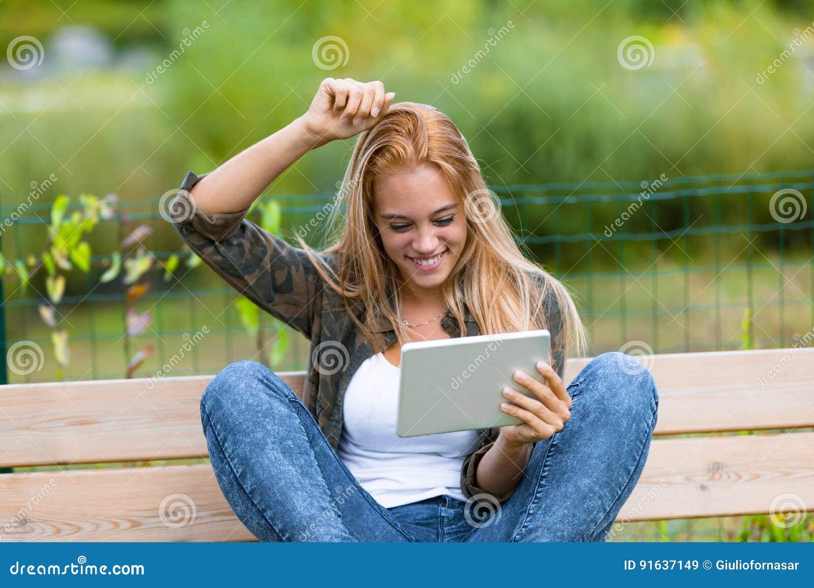 Muchacha feliz al aire libre con una tableta