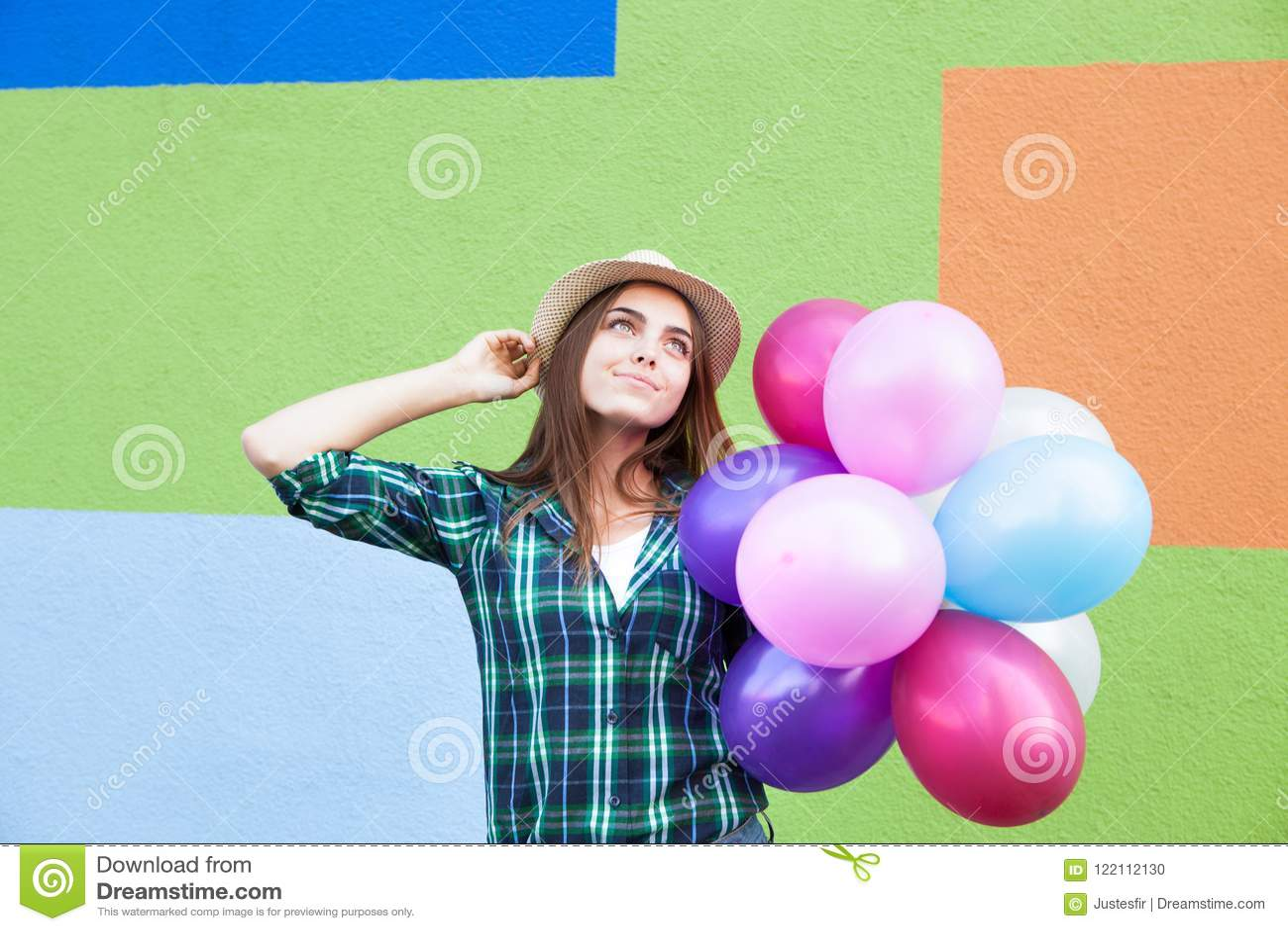 Muchacha feliz con las pecas con los globos que miran para arriba, cerca de la pared colorida en verano