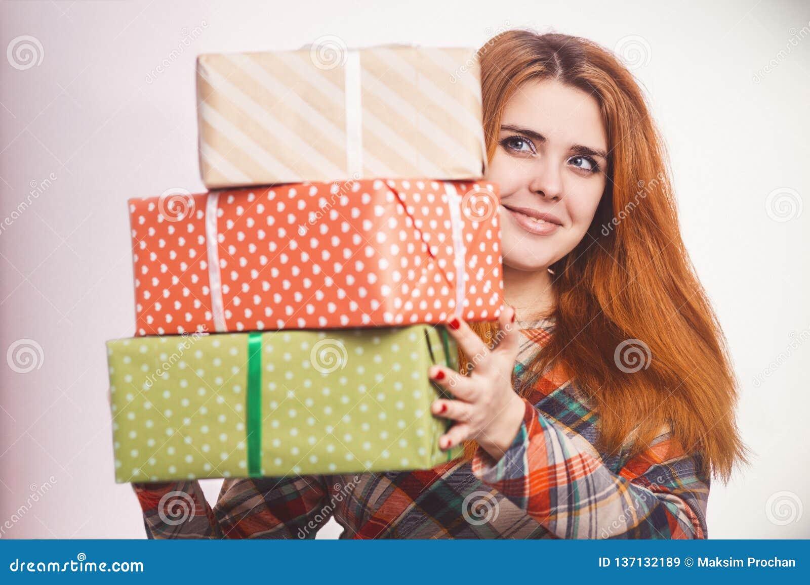 Muchacha feliz con las porciones de regalos en manos, de una mujer joven que sostiene una pila de cajas envueltas en papel decora