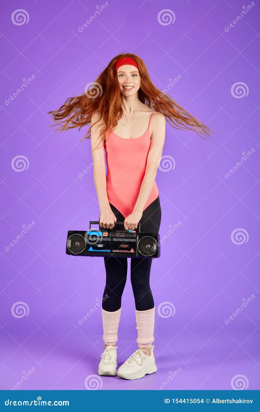 Muchacha feliz del estudiante con danza roja rizada larga del pelo con el reproductor de casete retro portátil
